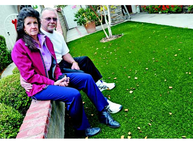 Saugus residents Dawn and Arthur DeVine-Pelt sit in front of their lawn. Months after they installed an artificial lawn in their front yard, the couple received a notice to appear before their local homeowner's association.