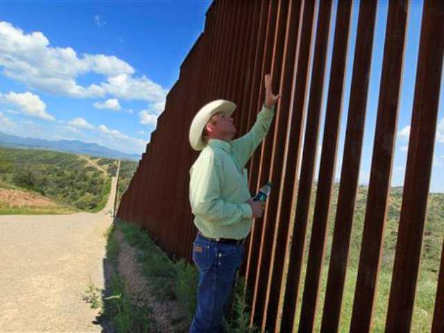 Rancher Dan Bell checks out part of the property he leases at the border fence between the United States and Mexico, in Nogales, Ariz.