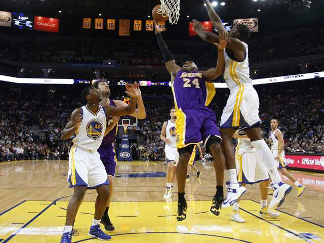 Los Angeles Lakers' Kobe Bryant (24) shoots next to Golden State Warriors' Festus Ezeli, right, and Harrison Barnes (40) during the first half  in Oakland Saturday.