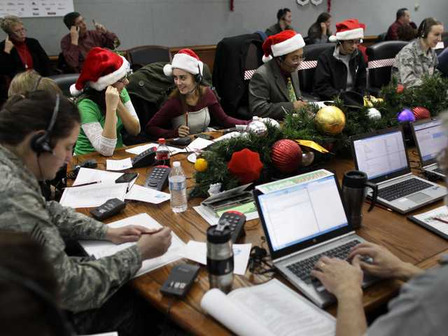 Lizzie Solano, center, and her sister Sarah take phone calls from children asking where Santa is and when he will deliver presents to their house, during the fifth annual NORAD Tracks Santa Operation, at the North American Aerospace Defense Command, or NORAD, at Peterson Air Force Base, in Colorado Springs, Colo., Monday.