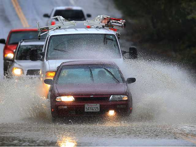 Cars are awash in floodwaters on Windsor Road at Pool Creek in Windsor, Friday during a winter storm.