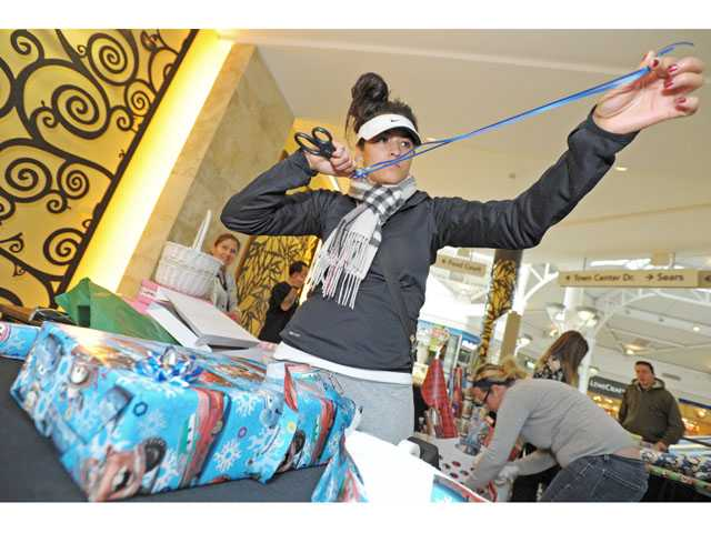 Olivia Garcia of Valencia wraps gifts at a booth at Westfield Valencia Town Center on Monday. (Jonathan Pobre/The Signal)