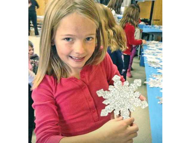 A student of Santa Clarita Elementary School with a snowflake she crafted for students of Sandy Hook Elementary School.