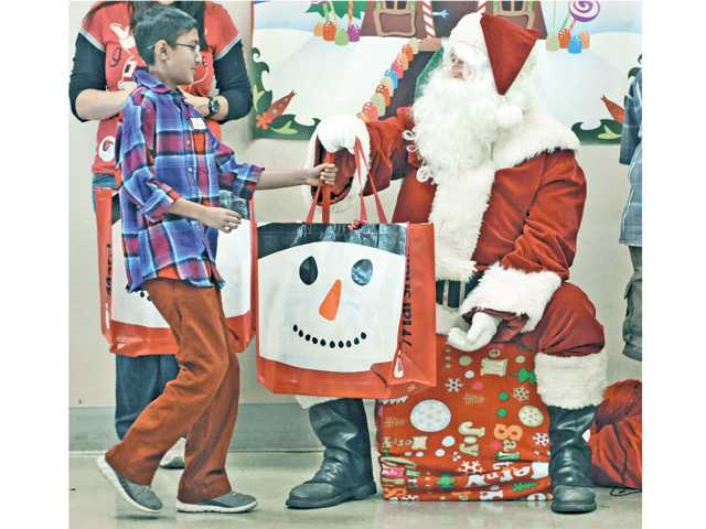 Syed Ali, 13, left, comes forward to collect his bag of Christmas gifts from Santa during the after school enrichment program's Christmas party hosted by The Santa Clarita Valley Association of Realtors at Newhall Elementary School in Newhall on Friday.