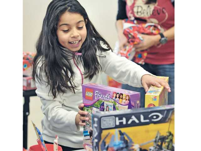Olga Delval, 8, unwraps the game she received from Santa during the after school enrichment program Christmas party hosted by The Santa Clarita Valley Association of Realtors at Newhall Elementary School in Newhall on Friday.