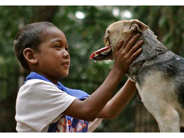A Bunggal family member plays with Kabang the dog in the Philippines.
