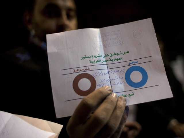 An Egyptian election worker shows his colleagues an invalid ballot while counting ballots.