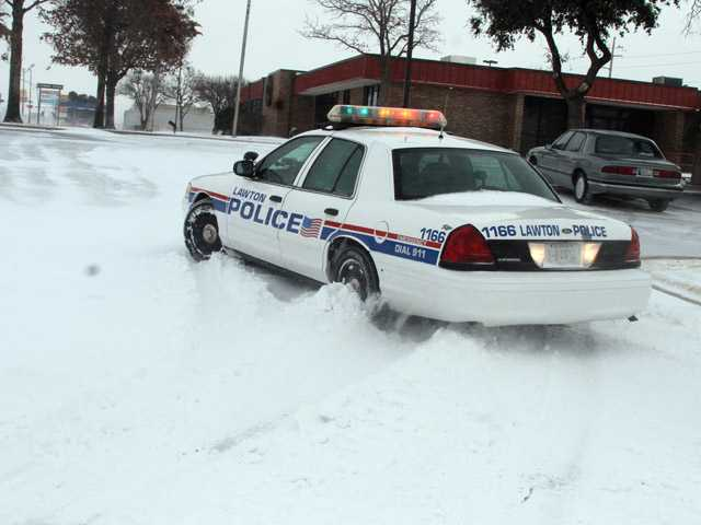 A Lawton, Okla., police cruiser tries to navigate the snow as blizzard conditions hit southwest Oklahoma at midday Tuesday.