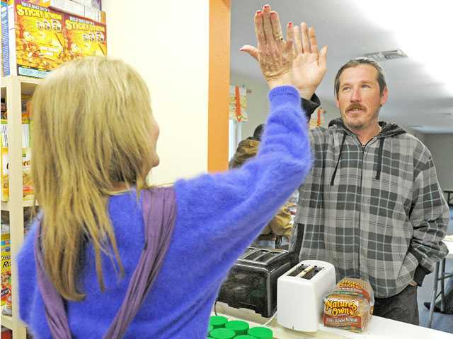 Terri Hansen of Saugus shares a high-five with Bryan Stubbins as she volunteers in the dining room of the Bridge To Home shelter in Saugus on Tuesday morning.