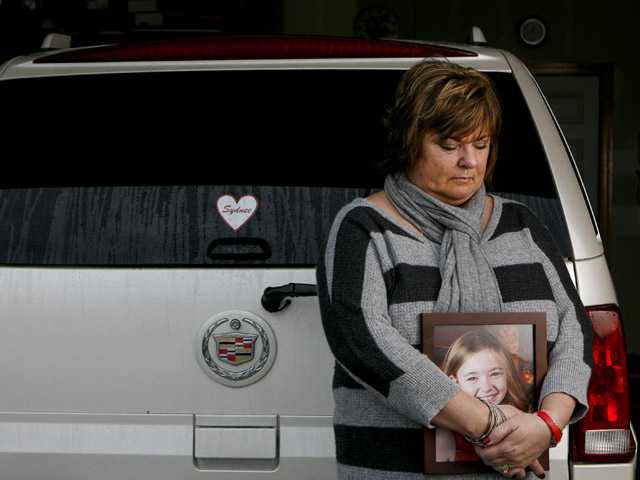Judy Neiman holds a photo of her daugher, Sydnee, in front of her 2006 Cadillac Escalade.