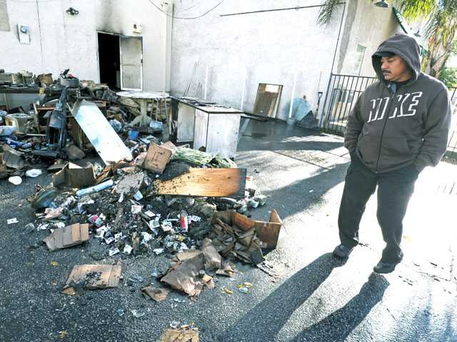 Freddy Jimenez looks at the debris pulled by firefighters to the rear of his sister's Newhall shop on Wednesday.