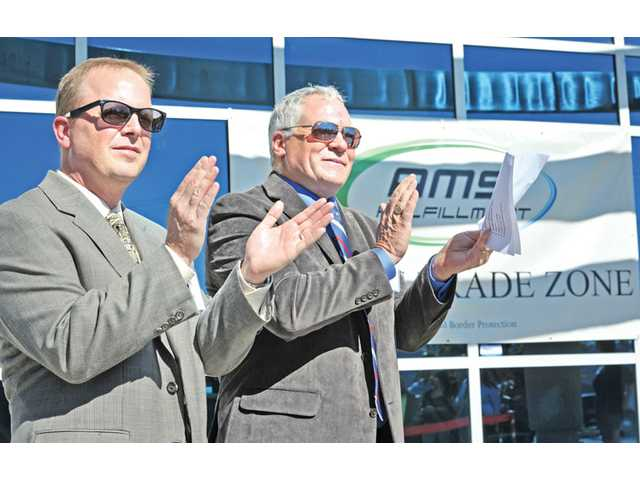 AMS managing partners, President Jay Catlin, left, and CEO Ken Wiseman clap at a ceremony introducing their foreign trade zone status at AMS offices in Castaic on Oct. 25.
