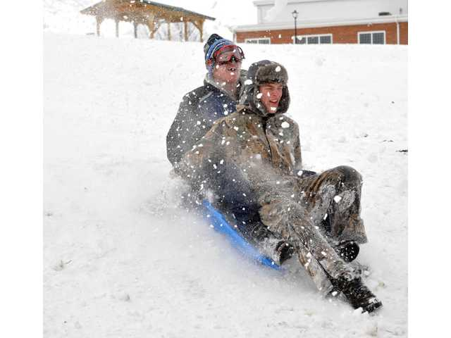 Michael Kuder, 17, of Pleasant Hill, and Luke Cameron, 16, of Troy double up on a sled run at Mote Park in Piqua, Ohio.