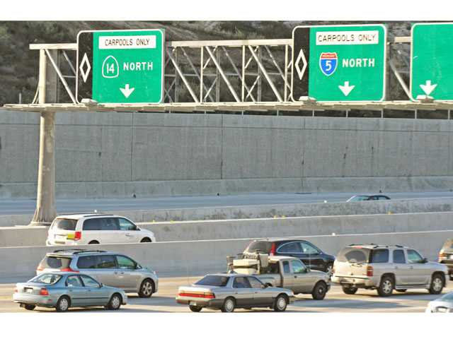 Motorists drive by signage for newly opened carpool lanes near the transition from northbound Interstate 5 to northbound Highway 14 in Sylmar on Wednesday.