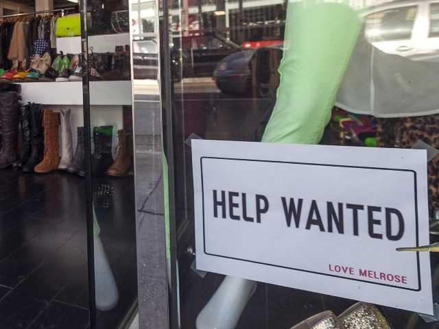 A help wanted sign is posted on the front window of a clothing boutique in Los Angeles.The number of Americans seeking unemployment benefits fell sharply, sign that the job market may be improving.
