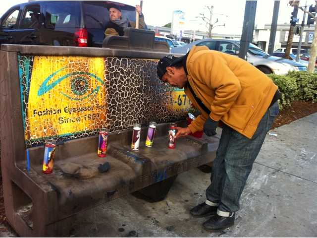 Phil Furtado places candles on a burned city bus bench in Los Angeles on Thursday Dec. 27,2012. Police arrested a man for allegedly setting a 67-year-old woman on fire who was sleeping on the bus stop bench. A witness said he saw a man come out of the store and pour something on the woman who had been sleeping on a bench before striking a match and setting her ablaze. The woman, who may be homeless, was taken to a hospital and listed in critical condition.