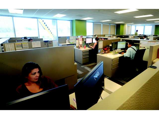 Precision Dynamics staff working on customer calls in August 2012 at the company's Valencia headquarters in Santa Clarita. Brady Corp. purhcased the company for $300 million in cash.