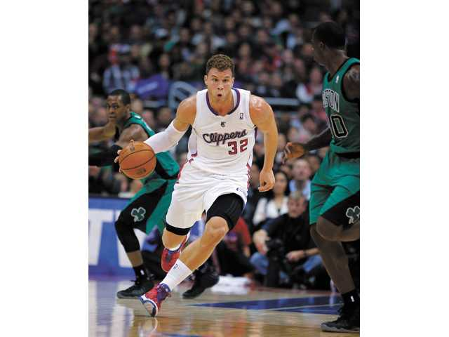 Los Angeles Clipper Blake Griffin, center, makes his way down the court against the Boston Celtics on Thursday in Los Angeles.