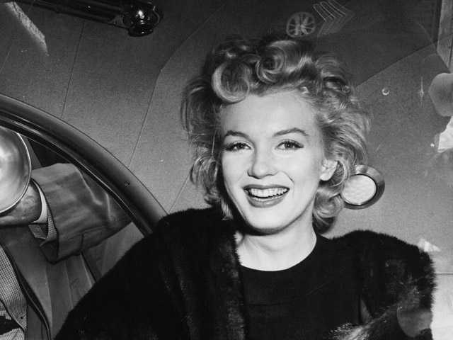 In this file photo, actress Marilyn Monroe smiles in a car after arriving tousled from an all-night plane flight from Hollywood to Idlewild Airport, in New York