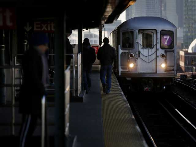 Commuters walk on the platform as a train enters the 40th St-Lowry St Station, where a man was killed after being pushed onto the subway tracks, in New York, Friday.