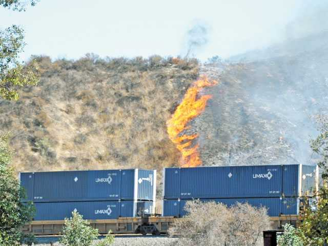 A freight train makes its way past a brush fire burning near Centre Pointe in Santa Clarita last October. The blaze Oct. 25 was one of the few wildfires in the Santa Clarita Valley in 2012.