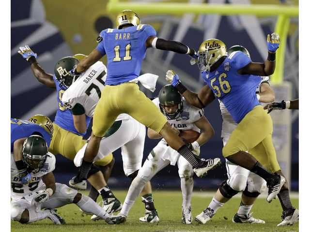Baylor quarterback Nick Florence, bottom center, looks for an escape route as UCLA linebackers swarm him on Thursday in San Diego.