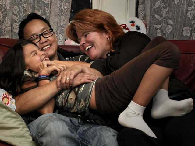 "In this Dec. 6 photo, partners MeiBeck ""Chino"" Scott-Chung, left, and Maya Scott-Chung, right, play with their 8-year-old daughter Luna at their Oakland home."