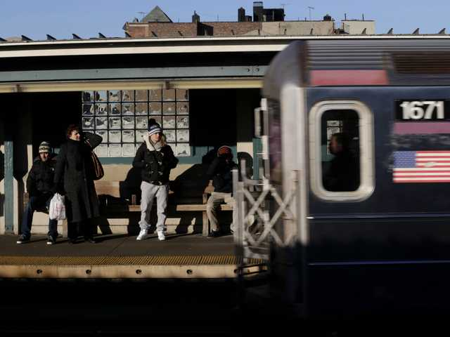Commuters watch as a train enters the 40th St-Lowry St Station, where a man was killed after being pushed onto the subway tracks, in the Queens section of New York, Friday.