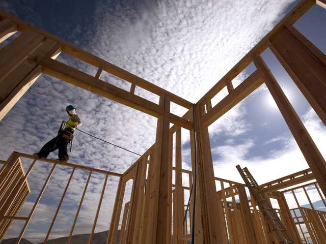 In this Nov. 16 photo, construction worker Elabert Salazar works on a house frame for a new home in Chula Vista.