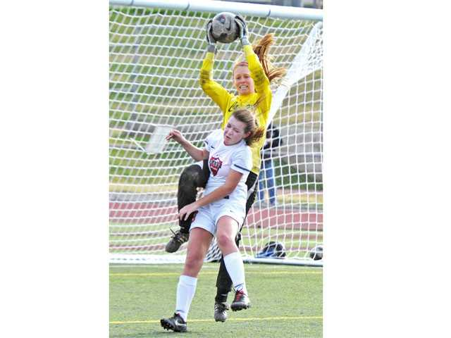 Canyon goalkeeper Meghan Kennedy makes a save behind Hart's Danielle Spickard (13) on Friday at Hart High.