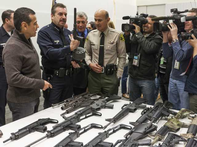 Los Angeles Mayor Antonio Villaraigosa, left, by some of the weapons collected in Wednesday's Los Angeles Gun Buyback event.