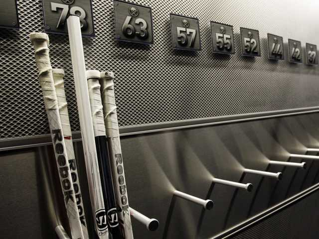 In this Sept. 25 file photo, a nearly empty hockey stick rack in the locker room of the Buffalo Sabres hockey team is shown during the NHL labor lockout in Buffalo, N.Y.