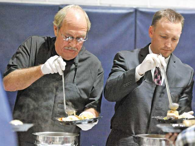 Don Fleming of Valencia Acura, left, and Ken Striplin, Santa Clarita city manager, ladle gravy onto plates of turkey and stuffing at the Boys & Girls Club of SCV in Canyon Country.