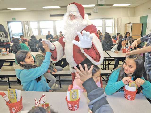 Santa gives high fives to students at Newhall Elementary School during a special event hosted by the Southland Association of Realtors SCV Chapter.