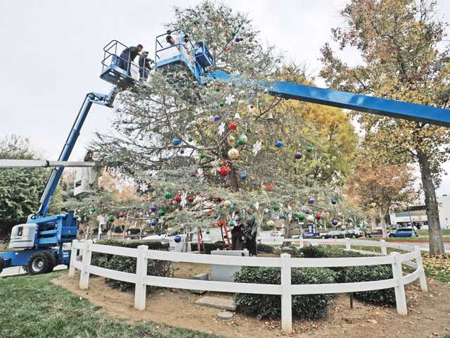 Volunteers hang lights and ornaments on the Community Tree.