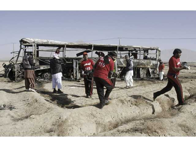 Pakistani volunteers carry a lifeless body out of a bus targeted in a suicide bombing in Quetta, Pakistan on Sunday.