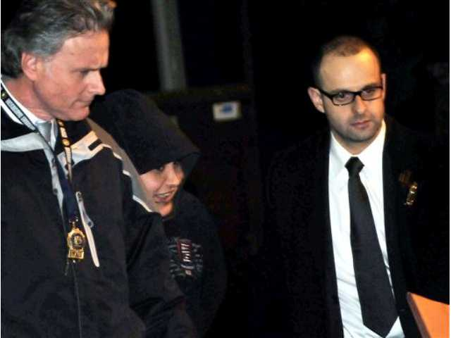 New York City Police Department detectives escort Erika Menendez, second from left, out of the 112th Precinct in the Queens borough of New York. Menendez was arraigned Saturday night on a charge of murder as a hate crime. Judge Gia Morris has ordered that the 31-year-old be held without bail and be given a mental health exam.