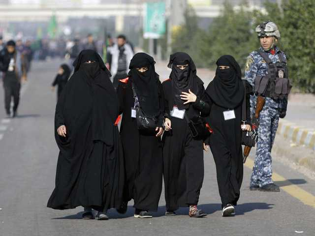 An Iraqi federal policeman stands guard as Shiite pilgrims marching to Karbala for Arbaeen in Baghdad on Monday.