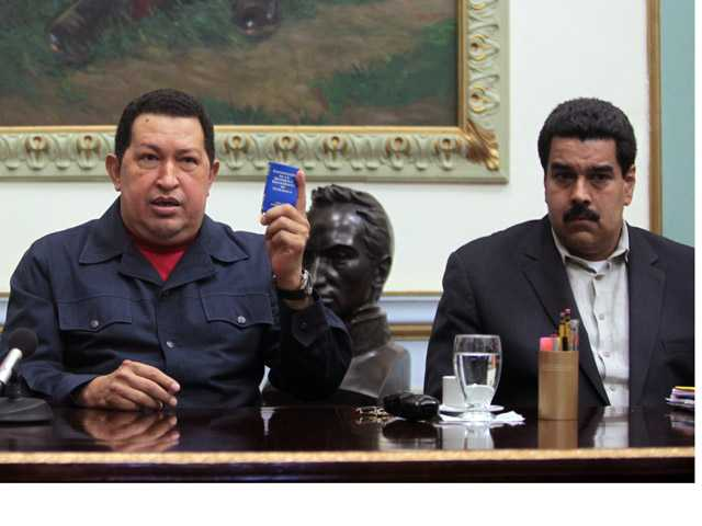 Venezuela's President Hugo Chavez, left, holds up a copy of the Venezuelan national constitution.