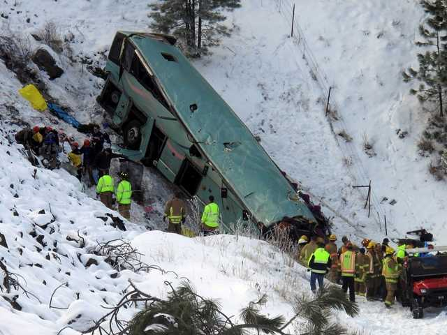 Emergency personnel respond to the scene of a multiple-fatality accident after a tour bus careened through a guardrail on an icy highway on Sunday.