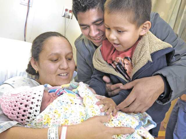 Mother Norma Polanco-Ramirez, left, holds her daughter, New Year's baby Keylen Elizabeth as father Oscar Ramirez and brother Kevin, 3, right, get a look at the first baby of 2013 born at Henry Mayo Newhall Memorial Hospital on Tuesday.