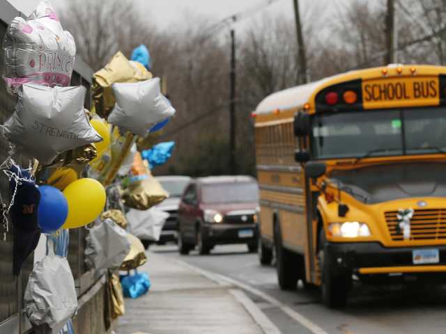 In this Dec. 18 file photo, a school bus rolls toward a memorial in Newtown, Conn., for victims of the Sandy Hook Elementary School shooting.