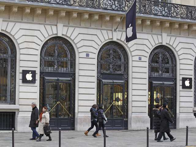 Parisians and tourists wander in front of the Apple store located near the Paris Opera, Tuesday. A robbery took place at the flagship store on Monday.