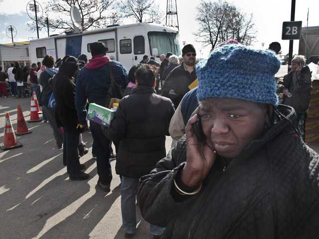 Evangean Pugh, far right, talks on a phone as she waits on line to apply for recovery assistance from Superstorm Sandy.