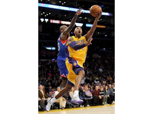 Los Angeles Lakers guard Kobe Bryant, right, shoots past Philadelphia 76ers guard Jason Richardson on Tuesday in Los Angeles.