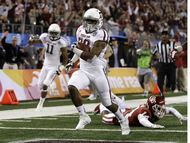 Texas A&M's Trey Williams runs past Oklahoma's Aaron Colvin, right, on the way to a touchdown during the second half of the Cotton Bowl on Friday in Arlington, Texas.