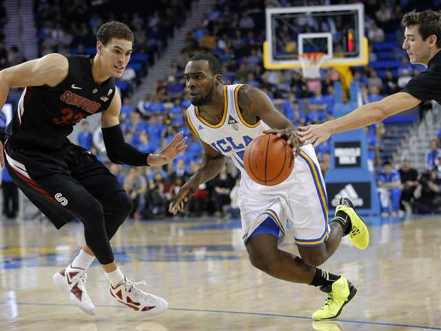 UCLA's Shabazz Muhammad, center, is defended by Stanford's Dwight Powell, left, and Rosco Allen during the second half in  Los Angeles on Saturday. UCLA won 68-60.