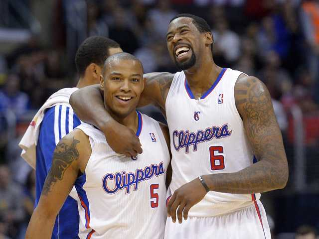 Los Angeles Clippers center DeAndre Jordan, right, hugs forward Caron Butler as they walk to the bench during a timeout on NBA basketball game against the Golden State Warriors on Saturday in Los Angeles.