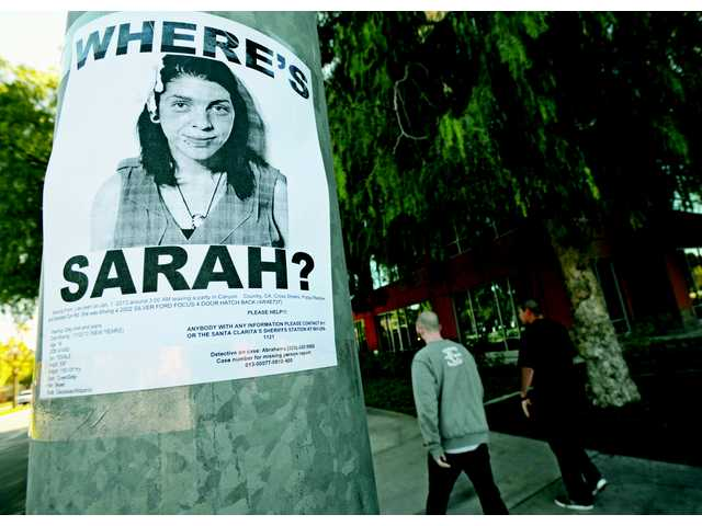 Friends and family of missing Sarah Alarid put up posters across town.