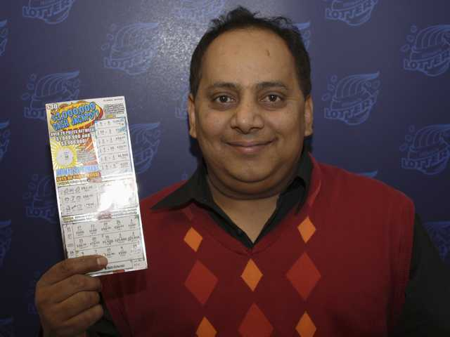 Urooj Khan, 46, of Chicago's West Rogers Park neighborhood, posing with a winning lottery ticket. The Cook County medical examiner said Monday, that Khan was fatally poisoned with cyanide July 20, 2012, a day after he collected nearly $425,000 in lottery winnings.
